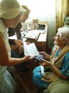 oben: Freiwillige übergeben Lebensmittel und Geschenke an eine Holocaustüberlebende